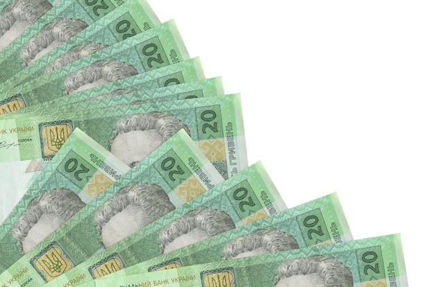 Банкноты 20 украинских гривен лежат изолированно на белой стене с копией пространства, сложенными в веер крупным планом. понятие времени выплаты жалованья или финансовые операции