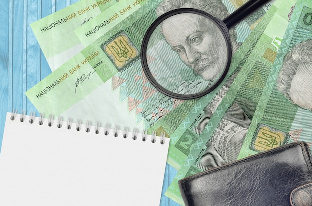 20 ukrainian hryvnias bills and magnifying glass with black wallet