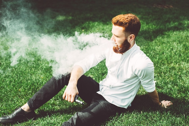 20 year old guy in a white shirt sitting on the grass and vaping.