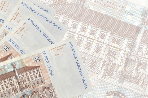 200 croatian kuna bills lies in stack on wall of big semi-transparent banknote. abstract business wall with copy space