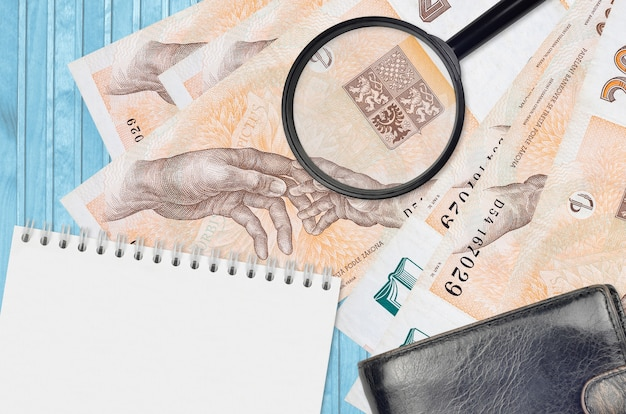 200 czech korun bills and magnifying glass with black purse and notepad. concept of counterfeit money. search for differences in details on money bills to detect fake money