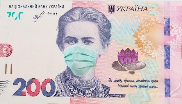 수평 의료 마스크에 lesya ukrainka와 200 hryvnia 지폐. 경제 위기는 우크라이나에 영향을 미쳤습니다. 우크라이나어 돈, 코로나 바이러스 개념, 몽타주, 닫습니다. 우크라이나의 covid-19 코로나 바이러스.