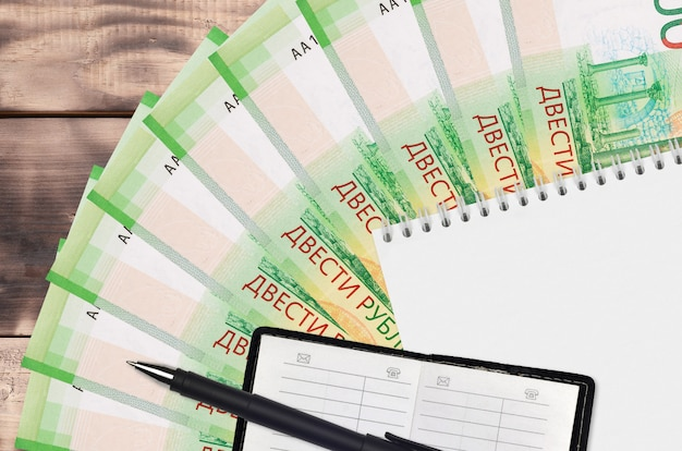 200 russian rubles bills fan and notepad with contact book and black pen. concept of financial planning and business strategy
