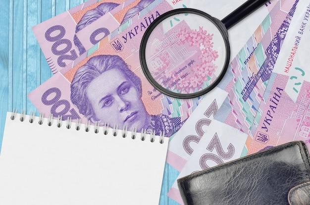 Банкноты 200 украинских гривен и увеличительное стекло с черным кошельком и блокнотом. понятие о поддельных деньгах.