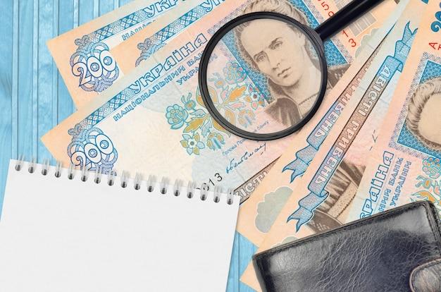 Банкноты 200 украинских гривен и увеличительное стекло с черным кошельком и блокнотом