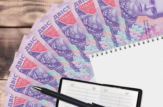 200ウクライナフリヴニアの法案のファンとメモ帳と連絡帳と黒のペン。財務計画と事業戦略の概念