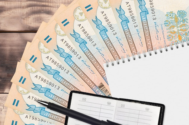 200 ukrainian hryvnias bills fan and notepad with contact book and black pen