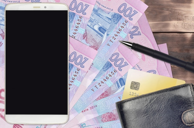 200 ukrainian hryvnias bills and smartphone with purse and credit card. e-payments or e-commerce concept. online shopping and business with portable devices