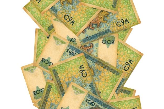 200のウズベキスタンのソム紙幣が白で隔離されて飛んでいます。多くの紙幣が左右に白いコピースペースで落ちています