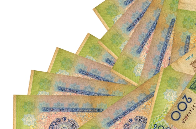 200 uzbekistani som bills lies in different order isolated on white. local banking or money making concept.