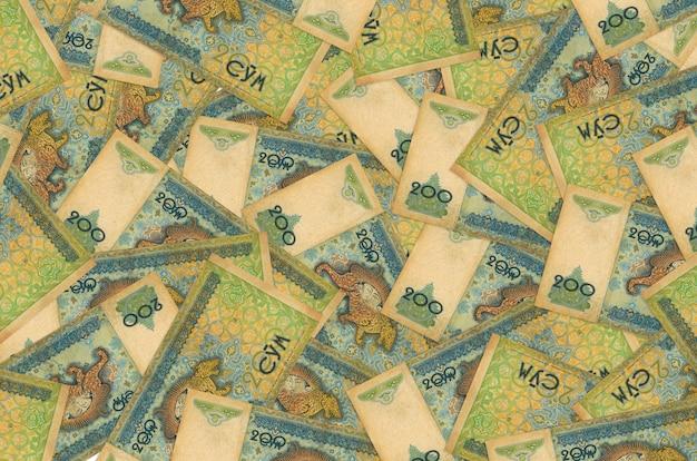 Купюры в 200 узбекских сомов лежат большой стопкой. концептуальная стена богатой жизни. большая сумма денег