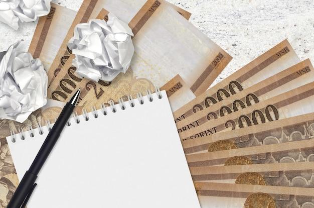2000ハンガリーのフォリント紙幣と空白のメモ帳でしわくちゃの紙のボール。悪いアイデア以下のインスピレーションのコンセプト。投資のアイデアを探す