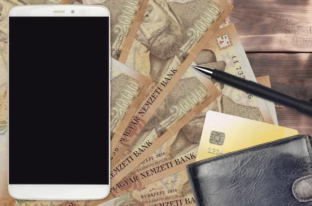 2000ハンガリーフォリント紙幣と財布とクレジットカード付きのスマートフォン