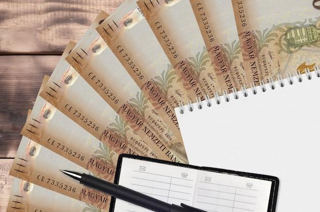 2000ハンガリーのフォリント紙幣ファンとメモ帳、連絡帳と黒ペン。財務計画と事業戦略の概念