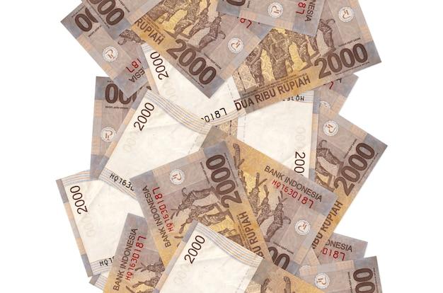 Банкноты 2000 индонезийских рупий, летящие вниз, изолированные на белом. многие банкноты падают с белым пространством для копирования слева и справа