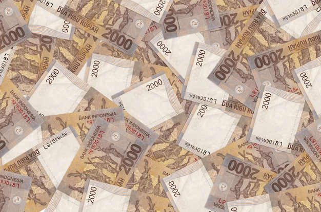 Банкноты в 2000 индонезийских рупий лежат большой стопкой. . большая сумма денег