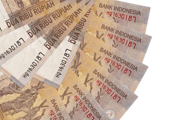 2000 인도네시아 루피아 지폐는 팬 모양에 쌓인 복사본 공간이 흰 벽에 고립 된 거짓말을 닫습니다. 금융 거래 개념