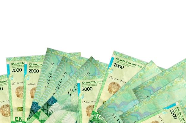 2000 카자흐스탄 텡게 지폐는 복사 공간이있는 흰 벽에 고립 된 화면의 아래쪽에 놓여 있습니다.