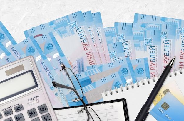 Банкноты 2000 российских рублей и калькулятор с очками и ручкой. концепция уплаты налогов или инвестиционные решения. финансовое планирование или бухгалтерские документы