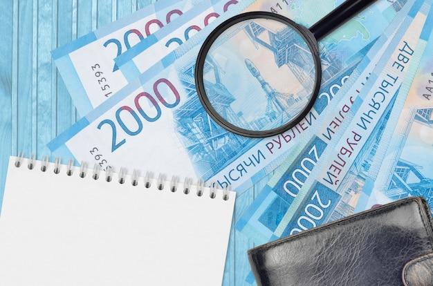 2000ロシアルーブル紙幣と黒い財布付きの拡大鏡