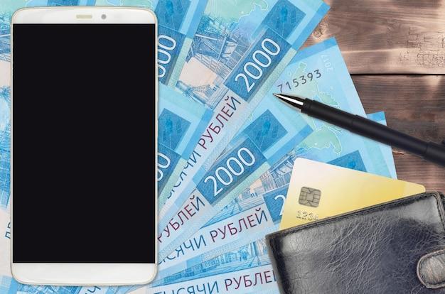 Купюры 2000 российских рублей и смартфон с кошельком и кредитной картой