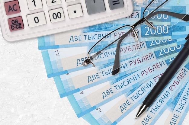 Вентилятор банкнот 2000 российских рублей и калькулятор с очками и ручкой. бизнес-ссуды или концепция сезона уплаты налогов. финансовое планирование
