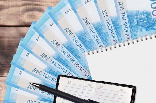 Вентилятор банкнот 2000 рублей и блокнот с записной книжкой и черной ручкой. концепция финансового планирования и бизнес-стратегии