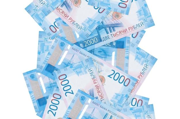 Банкноты 2000 российских рублей, летящие вниз, изолированные на белом. многие банкноты падают с белым пространством для копирования слева и справа