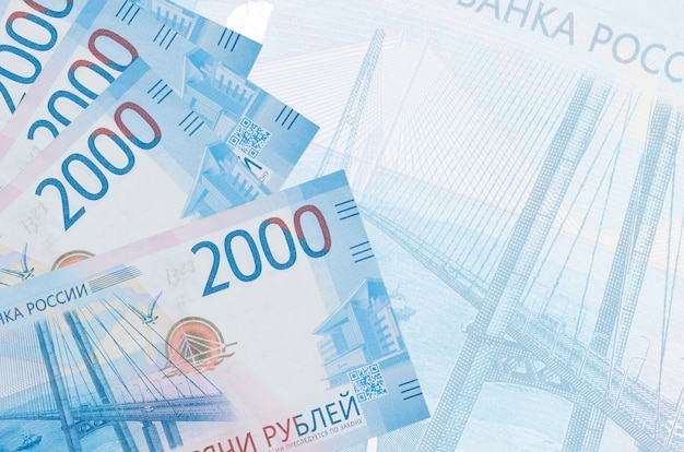 2000 russian rubles bills lies in stack on wall of big semi-transparent banknote.