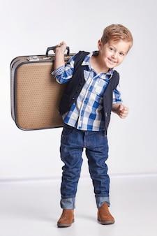 ロシアエカテリンブルク-2016年4月1日:スーツケースを持って立っている小さな男の子は、休暇に行きます。