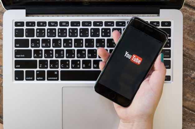 チェンマイ、タイ -  2017年10月1日:女性がiphone 6 sでyoutubeのスクリーンショットを表示します。古い木製の机の上に横たわる画面上のyoutubeアプリ。 youtubeは人気のあるオンラインビデオ共有webサイトです。
