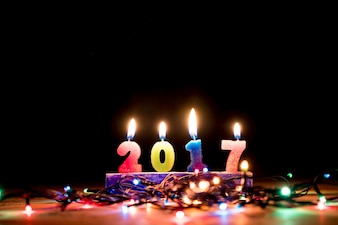 2017 candles numbers  with christmas lights on black background. New Year Concept