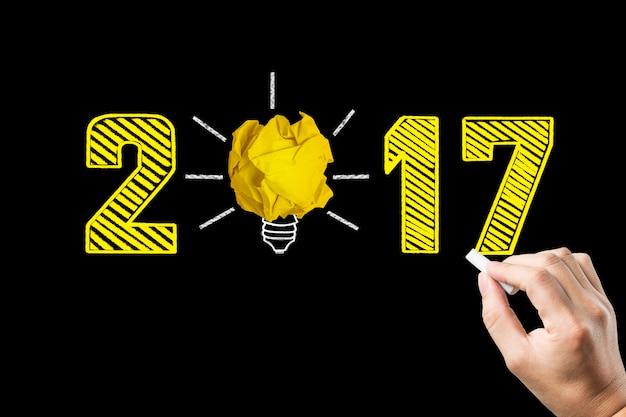 電球と黒板に手書き年2017