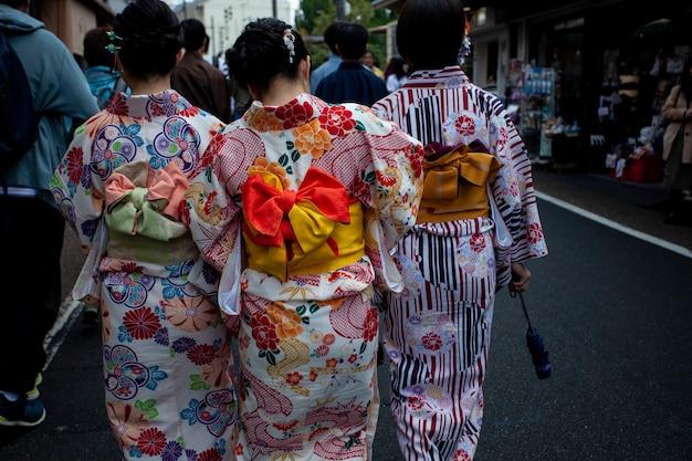 京都日本-2018年11月10日:伝統的な着物を着た正体不明の女性が京都で最も人気のある旅行先の1つである矢坂神社の通りを歩いています