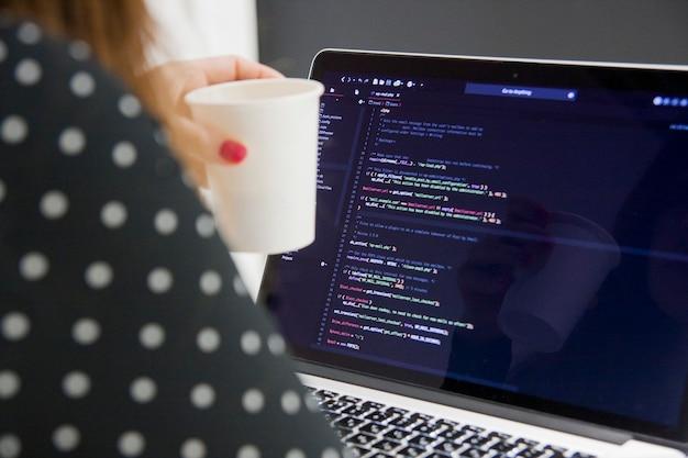 ロサンゼルス、カリフォルニア州、アメリカ合衆国-2018年12月27日:オフィスでラップトップコンピューターに取り組んでいるコーヒーカップを持つ女性プログラマー