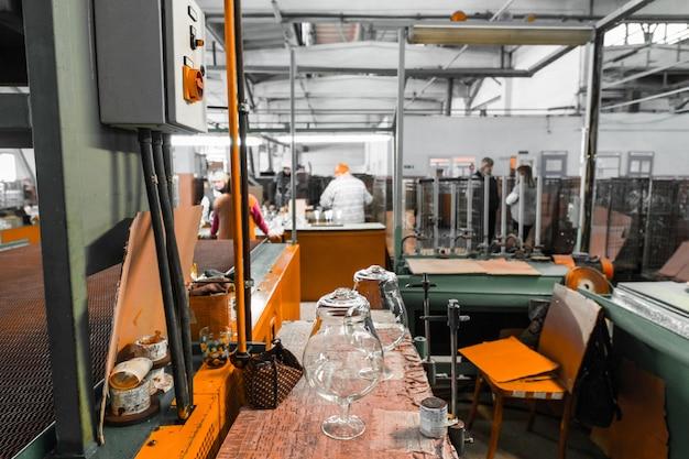 2018年2月1日、ベラルーシのミンスク:工場の壁で産業機器を扱うガラス生産労働者