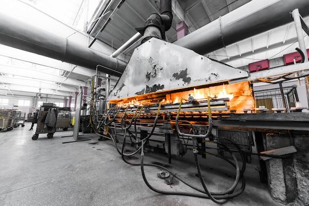 ベラルーシのミンスク、2018年2月1日:工場の壁で産業機器を扱うガラス生産労働者工場の壁で産業機器を扱うガラス生産労働者