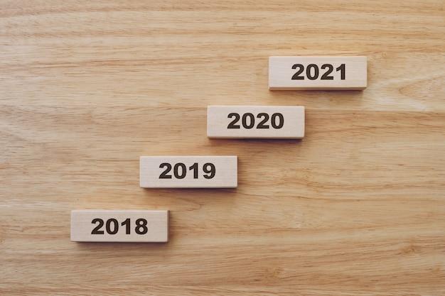 木のテーブルの背景にウッドブロックの2018年から2021年までの新年。新年のコンセプト