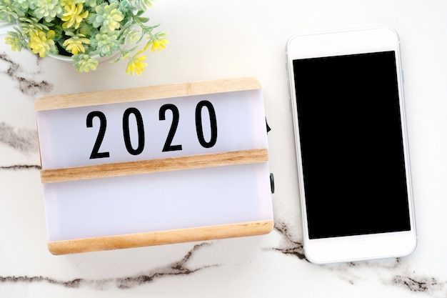 2018 on wood box and phone with blank screen on white marble table background