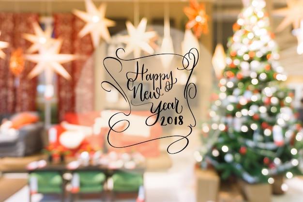 2018年カラフルなボケの幸せな新年のテキストは、装飾されたクリスマスツリーからぼやけた背景。