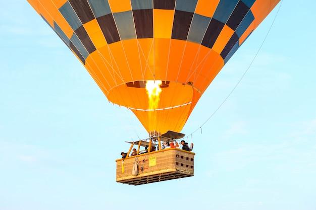 カッパドキア、トルコ-2019年10月19日:カッパドキアの谷の上を飛んでいる熱気球の観光客。熱気球はカッパドキアの伝統的な観光名所です。