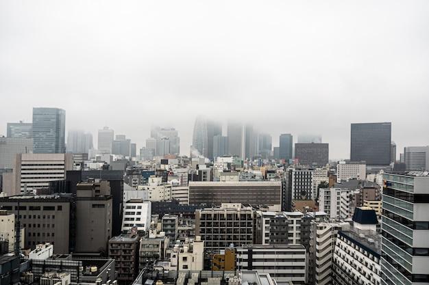 日本/東京-2019年10月29日:新宿の高層ビルのスカイラインの雲の上のトップビュー。日本の都市都市景観の不動産。