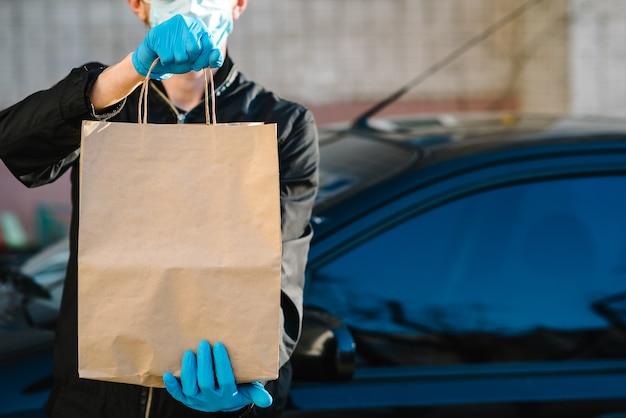 Курьер в защитной маске, медицинские перчатки доставляет еду на вынос. сотрудник держит картонную упаковку. место для текста. служба доставки под карантин, 2019-нков, пандемический коронавирус, ковид-19.