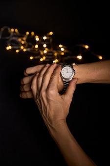 2019年の最初の1秒を迎えるために時計を見ている若い人の手