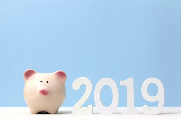 テーブルの上の木製の白い数2019とピンクの貯金箱。明けましておめでとう2019