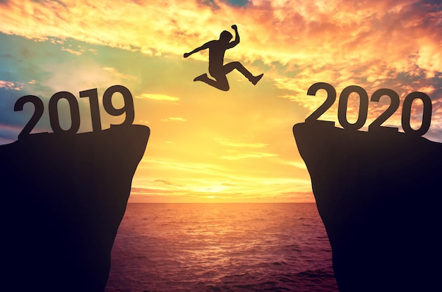Бизнесмен прыгает между 2019 и 2020 годами.