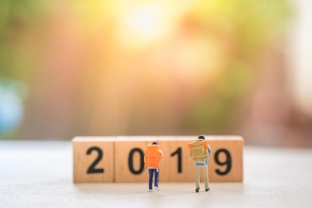 2019木製ナンバーブロックのスタックに歩くバックパックを持つ2つの旅行者のミニチュアフィギュア。