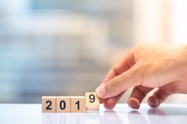 2019年を完了するために木製のブロック番号9を持っている手