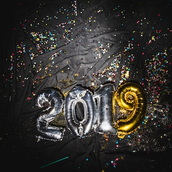 2019 balloons on dark fabric with confetti