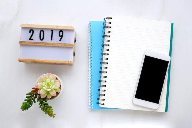 2019 , blank notebook paper and smart phone with blank screen on white marble table backgr